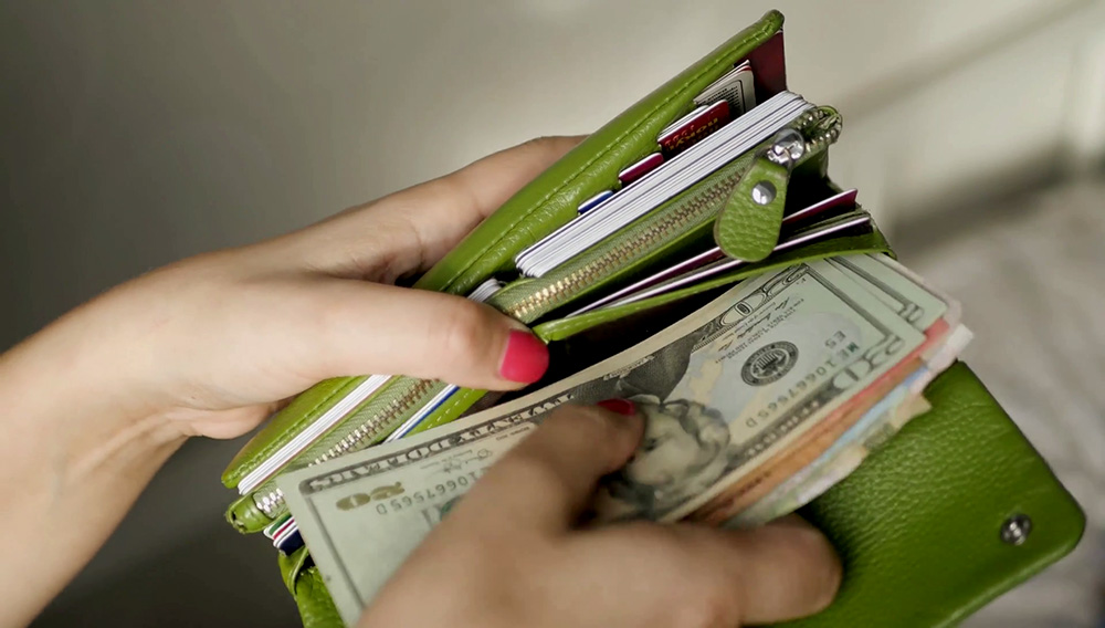 Girl with pink nail opening her green purse with credit cards and money from different countries