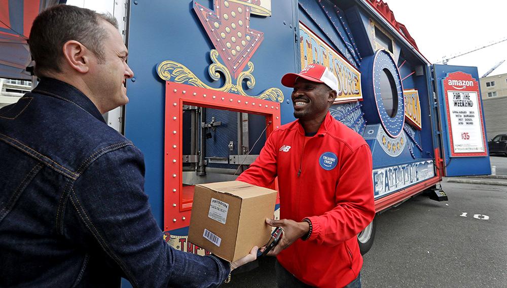 Empleado de Amazon atiende a un cliente que ha comprado en uno de los camiones de la empresa.