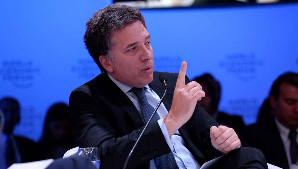 Nicolás Dujovne, ministro de Hacienda de Argentina, sentado hablando durante un evento, con el dedo índice de la mano derecha levantado.