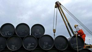 Un trabajador trabaja transportando barriles de petróleo.