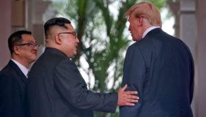 Kim Jong Un y Donald Trump de espaldas a la cámara, con árboles de fondo, Kim le toca el brazo izquierdo a Trump.
