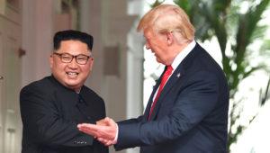 Líder de Corea del Norte, Kim Jong Un, con una amplia sonrisa, estrecha la mano del presidente de Estados Unidos, Donald Trump, quien lo mira e invita a caminar.