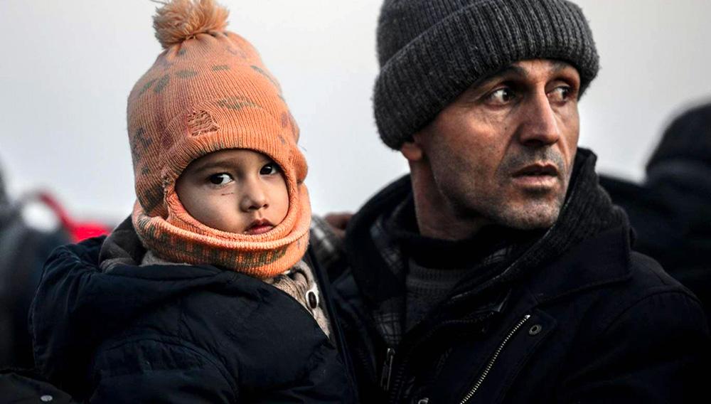 Inmigrante con un niño en brazos.