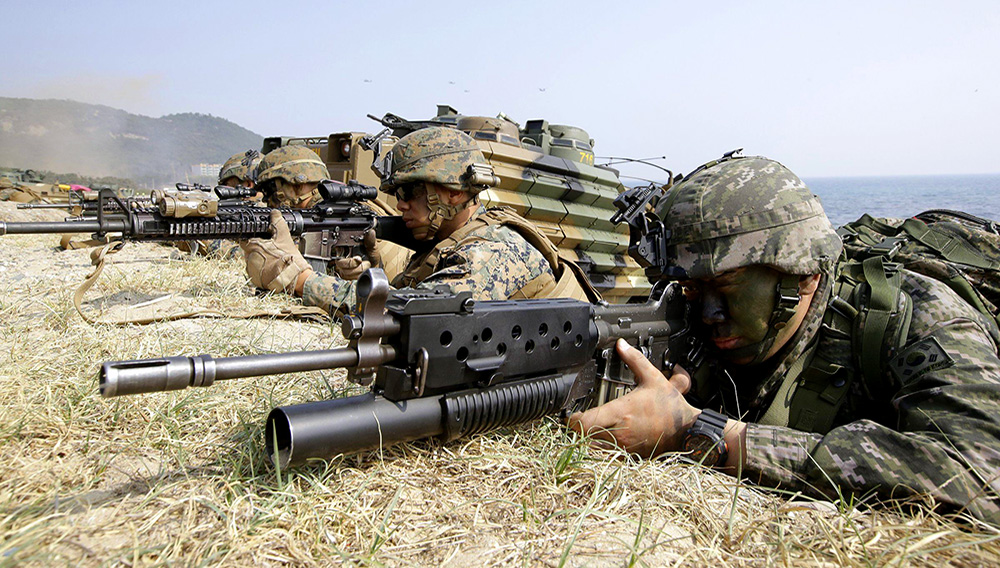 In this March 30, 2015, file photo, marines of South Korea, right, and the U.S aim their weapons near amphibious assault vehicles during U.S.-South Korea joint landing military exercises.