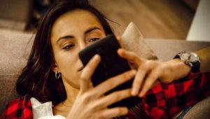 Mujer joven de cabellos largos y camisa roja y negra observa con atención su teléfono inteligente recostada en un mueble.