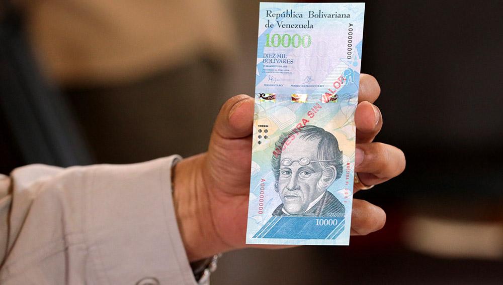Una mano mostrando un billete de 10,000 bolívares.