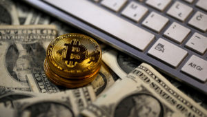 FILE PHOTO: Bitcoin (virtual currency) coins placed on Dollar banknotes, next to computer keyboard, are seen in this illustration picture, November 6, 2017. REUTERS/Dado Ruvic/Illustration/File Photo