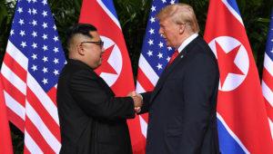 Líderes de Estados Unidos y Corea del Norte, Donald Trump y Kim Jong Un, se estrechan la mano en Singapur con las banderas de ambos países como fondo.