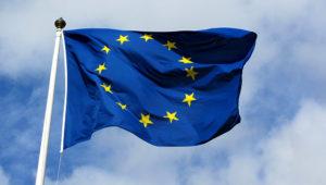 Bandera de la Unión Europea flameando delante de un cielo azul con nubes.