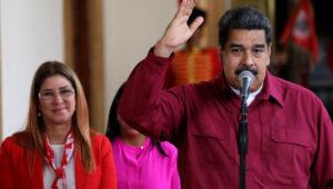 Nicolás Maduro hablando a través de un micrófono, con una camisa roja, el brazo derecho en alto y la mano abierta, al lado de su sonriente esposa Cilia Flores.