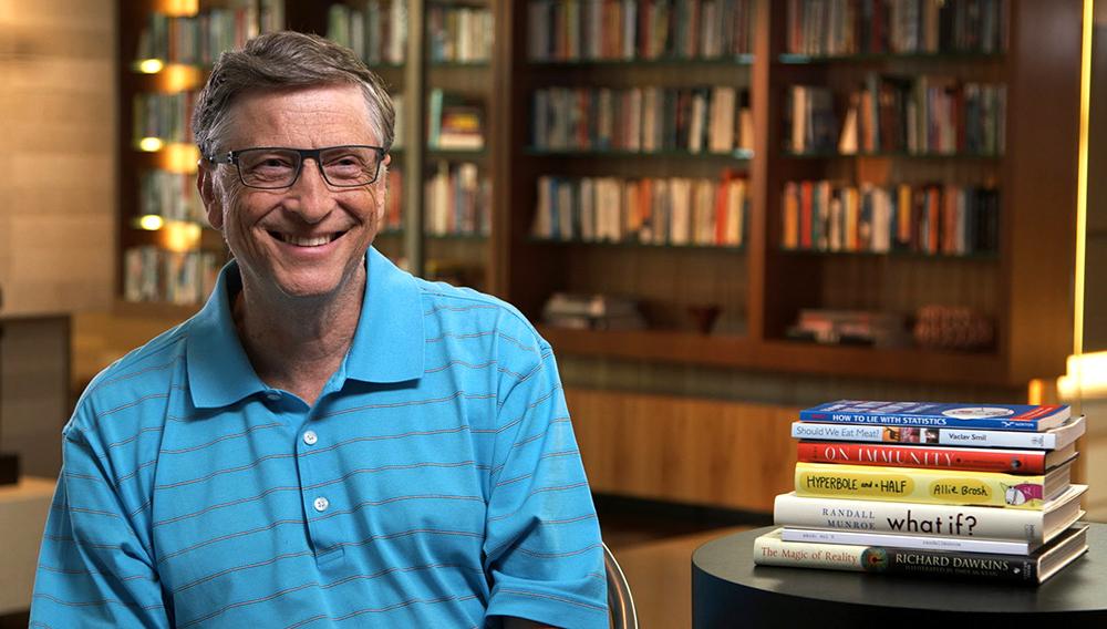 Bill Gates sonriendo en su biblioteca personal, junto con un grupo de libros en su mesa. Foto: The Gates Notes.