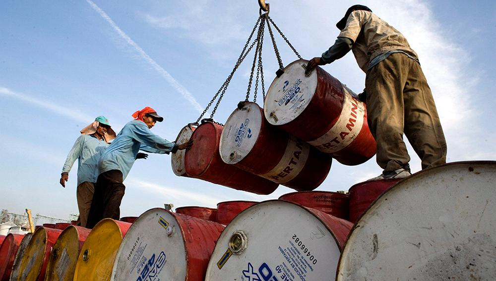 Dos operarios indonesios descargan barriles cargados de petróleo de la compañía Pertamina en el puerto de Yakarta, Indonesia, el 21 de septiembre. EFE/Adi Weda.
