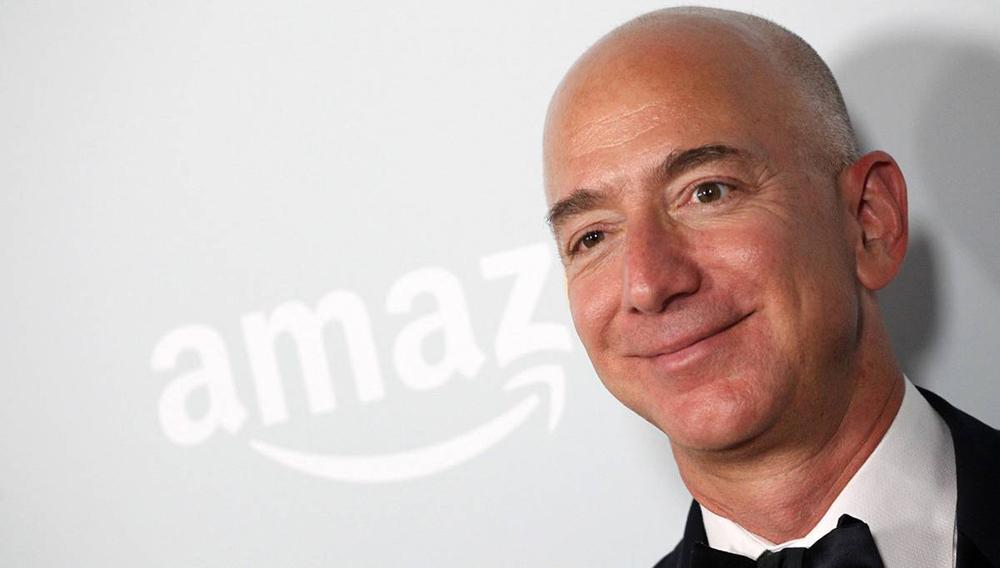 Jeff Bezos, CEO de Amazon, a la derecha, con el logotipo de su empresa, de fondo, a la izquierda.