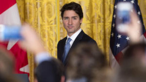 Justin Trudeau, primer ministro de Canadá, frente a periodistas, con una cortina amarilla de fondo.