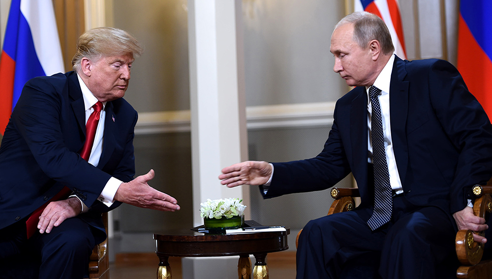 US President Donald Trump (L) and Russian President Vladimir Putin reach to shake hands before a meeting in Helsinki, on July 16, 2018. / AFP PHOTO / Brendan Smialowski