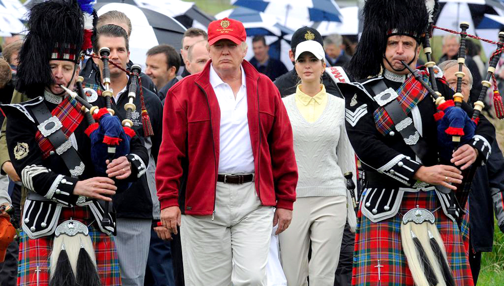 A picture taken on July 10, 2012 shows US tycoon Donald Trump (C) escorted by Scottish pipers as he officially opens his new multi-million pound Trump International Golf Links course in Aberdeenshire, Scotland. Over 70,000 people had on December 9, 2015 signed a petition to ban US presidential hopeful Donald Trump from entering Britain following his call to bar Muslims from entering the United States. AFP PHOTO / Andy Buchanan