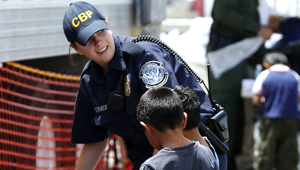 A U.S. Customs and Border Protection officer helps two young boys pick out clothes June 18, 2014, as they join hundreds of mostly Central American immigrant children being processed and held at the U.S. Customs and Border Protection placement center in Nogales, Ariz. (Photo: Ross D. Franklin, AP)