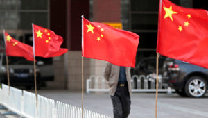 A man walks past Chinese national flags tied to iron fences at Chaoyang Hospital, where blind activist Chen Guangcheng was reported to be staying at, in Beijing May 2, 2012. REUTERS/Jason Lee
