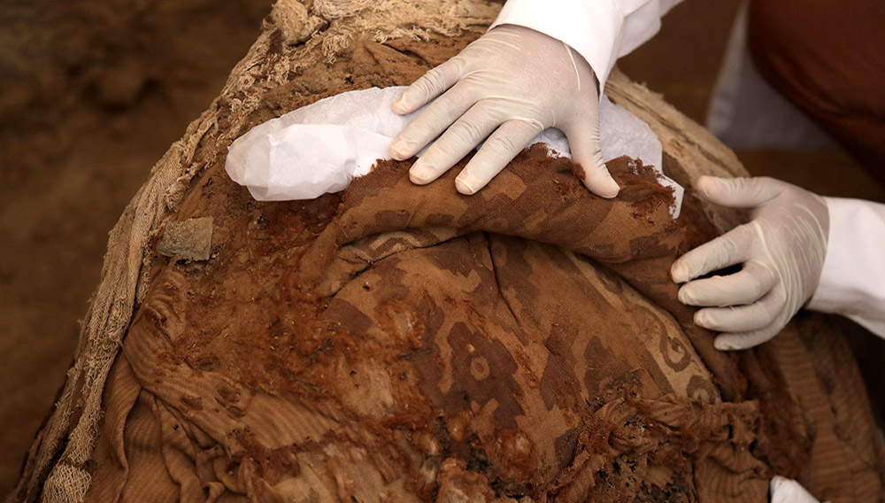 Un arqueólogo trabaja con un fardo funerario hallado en Túcume, Perú. Foto EFE.