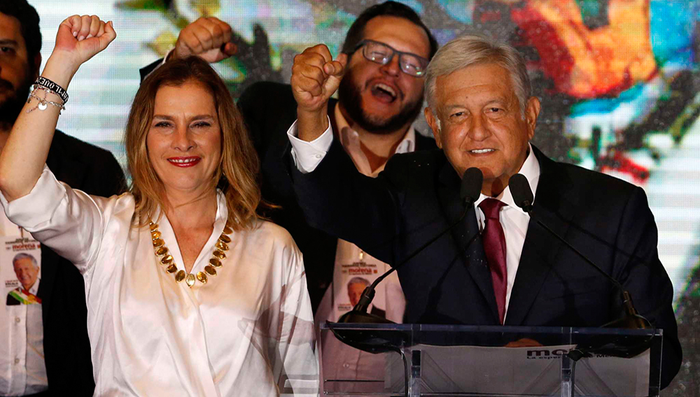 Presidential candidate Andres Manuel Lopez Obrador waves to supporters as he gives his first victory speech at his campaign headquarters at the Hilton hotel in Mexico City, Sunday, July 1, 2018. Lopez Obrador has claimed victory in Mexico's presidential election, calling for reconciliation. At left is his wife,Beatriz Gutierrez Muller. (AP Photo/Marco Ugarte)