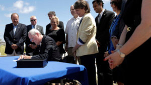 Lawmakers stand by as New Jersey Gov. Phil Murphy, center, signs a bill banning smoking on parks and beaches on the boardwalk in Long Branch, N.J., Friday, July 20, 2018. JULIO CORTEZ / AP PHOTO