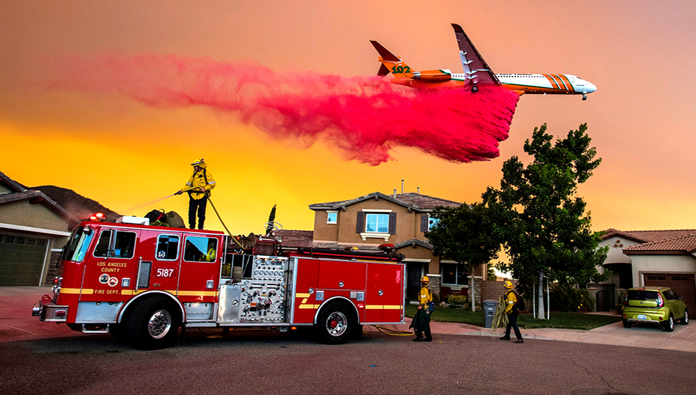 A plane drops fire retardant behind homes along McVicker Canyon Park Road in Lake Elsinore as the Holy fire burned near homes on Wednesday afternoon, August 8, 2018. (Photo by Mark Rightmire, Orange County Register/SCNG)