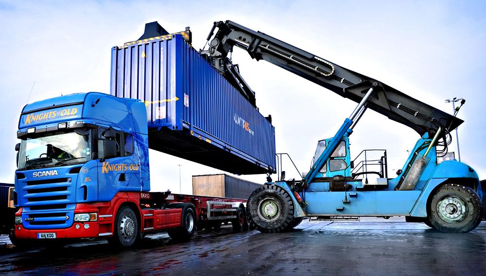 Una grúa levanta un contenedor de carga marítima y lo coloca sobre un camión Scania, en un terminal de contenedores.