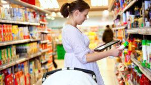 Mujer joven embarazada con una tablet en la mano comparando precios en un supermercado (Foto: Tyler Olson – Simplefoto)