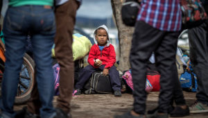 Venezuelan boy waits while his parents stay in line to get permission to inmigrate to Brazil. Photo: Andre Coelho.