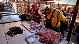 En esta imagen, tomada el 19 de agosto de 2018, un cliente huele una pieza de carne podrida en un mercado en Maracaibo, Venezuela. Los venezolanos hacen fila en uno de los mercados más grandes del país para comprar carne en mal estado. Algunos caen enfermos por tomar la carne estropeada, que se vende a precios muy bajos y es la única forma de poder comprar proteína ante la profunda crisis que vive el país. (AP Foto/Fernando Llano)