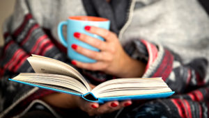 woman reading a book and holding a mug of hot beverage; Shutterstock ID 326453363; PO: today.com