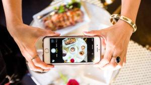 Manos de una mujer tomando una fotografía a un plato de comida con un smartphone desde arriba. Foto: cyneats