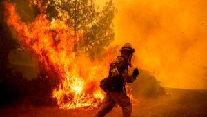 Un bombero corre para tratar de salvar una casa de un incendio forestal en Lakeport, California, el martes 31 de julio del 2018. (AP Foto/Noah Berger)