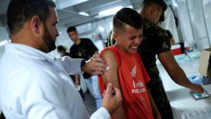 Un niño venezolano recibe vacunación gratuita de parte de un voluntario tras exhibir su pasaporte en el control fronterizo de Pacaraima, en el estado brasileño de Roraima, 9 de agosto de 2018. REUTERS/Nacho Doce