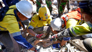 Rescue workers extract a woman, who survived after being trapped in rubble since the earthquake in Lombok, Indonesia. Antara Foto/Ahmad Subaid/Reuters