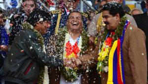 Los mandatarios de Bolivia, Evo Morales (iz.) y de Venezuela, Nicolás Maduro (der.) se saludan mientras el entonces presidente ecuatoriano Rafael Correa ríe en la ceremonia de bienvenida a los delegados del G77+China en Santa Cruz, Bolivia, el 14 de junio del 2014. AP.