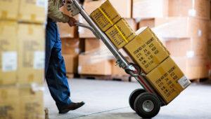 Empleado de logística una empresa llevando cajas con mercadería.