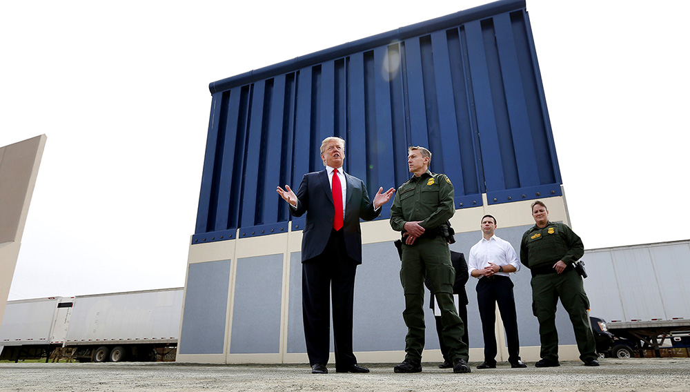 President Donald Trump speaks during a tours as he reviews border wall prototypes, Tuesday, March 13, 2018, in San Diego, as Rodney Scott, the Border Patrol's San Diego sector chief, listens. (AP Photo/Evan Vucci)