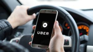 Hombre conduciendo un automóvil mirando un teléfono móvil donde se aparece el logotipo de Uber.