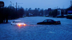 An abandoned car's hazard lights continue to flash as it sits submerged in rising flood waters during pre-dawn hours Saturday after Florence struck in Wilmington. PHOTO: JONATHAN DRAKE/REUTERS