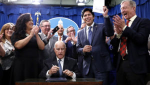 State Sen. Kevin de León (D-Los Angeles) holds up his environmental measure Senate Bill 100 after it was signed into law by Gov. Jerry Brown on Monday in Sacramento. (Rich Pedroncelli / Associated Press)