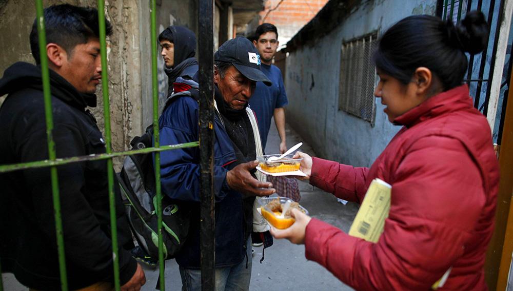 Esta foto del 6 de septiembre del 2018 muestra a personas haciendo fila para recibir una porción de comida afuera de un comedor popular ubicado en un centro comunitario en el barrio marginal Villa 1-11-14, en las afueras de Buenos Aires, Argentina. (AP Foto/Natacha Pisarenko)