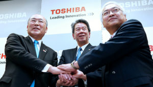 Toshiba's top-three executives, from left to right, Chairman Atsutoshi Nishida, President Hisao Tanaka and Vice Chairman Norio Sasaki give a handshake, hiding their feud against each other. (Job titles as of 2013. Photo by Kosaku Mimura)