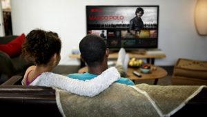 Un hombre y una mujer en una sala de estar viendo Netflix en un televisor grande. Image Credit: Netflix.com