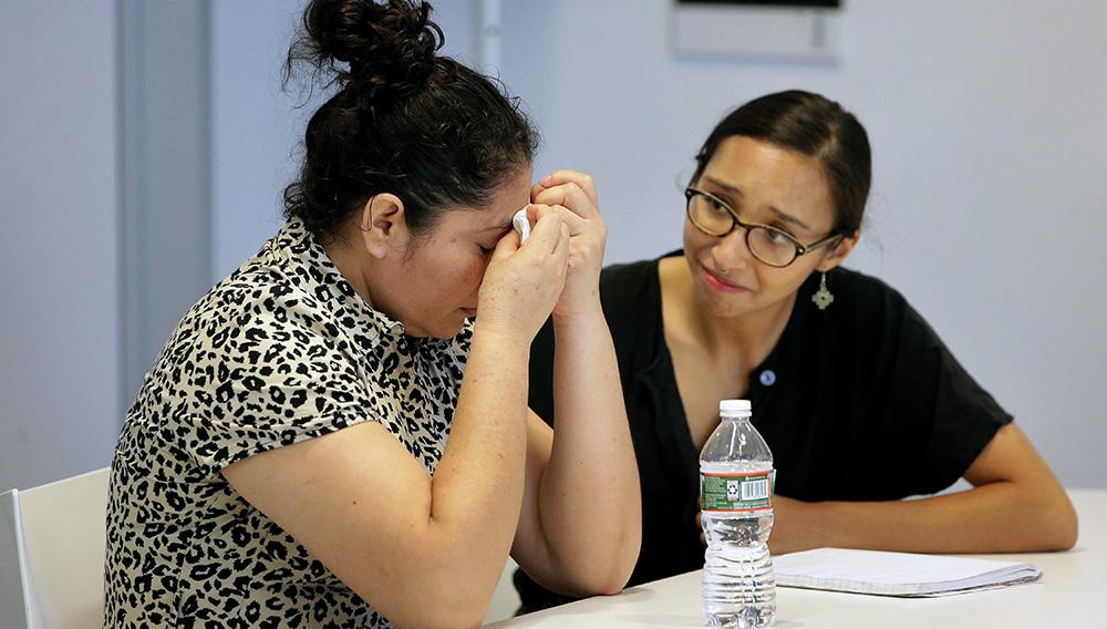 Una guatemalteca identificada solo como L.J. es consolada por la traductora Brenda Quintana (derecha) luego de ofrecer una conferencia de prensa en la que habló de haber sido separada de su hijo, el 6 de septiembre del 2018 en Boston. L.J. es una de las personas que demandaron al gobierno de Donald Trump, exigiendo compensaciones por los traumas que padecen los niños que fueron separados de sus padres al ingresar ilegalmente de México a Estados Unidos. (AP Foto/Steven Senne)