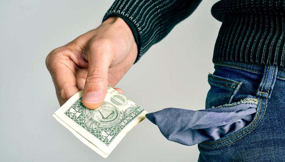 Foto de archivo - Un hombre caucásico joven en pantalones vaqueros toma un dólar de su bolsillo. 123rf.com