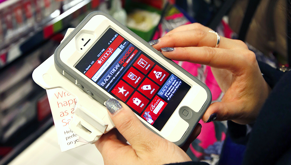 Tashalee Rodriguez, of Boston, uses a smartphone app while shopping at Macy's in downtown Boston. For the first time, analysts predicted that more than half of online traffic to retailer sites would come from smartphones than desktops during the busy Black Friday holiday shopping weekend. (Associated Press)