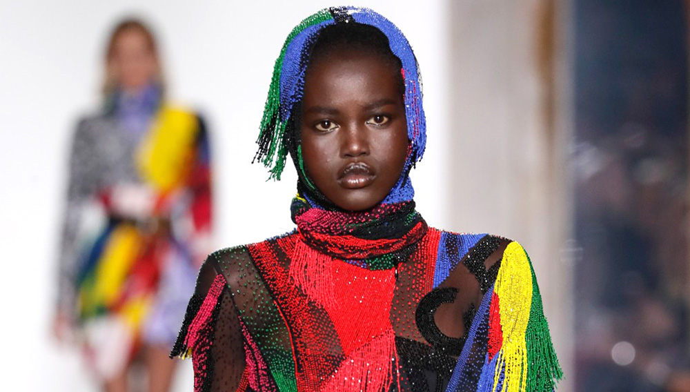 Model Adut Akech presented a wild Versace creation of swirling colors topped by a hood on the Fall 2018 catwalk - Feb 23, 2018.