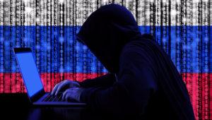 Hacker escribiendo en una laptop con la cabeza oculta con una capucha, con la bandera de Rusia al fondo.