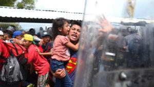 Un migrante hondureño con una menor en brazos grita hacia los miembros de la policía mexicana en el paso fronterizo entre Guatemala y México en Tecún Umán, Guatemala. EFE